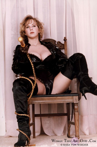 Fiery haired blonde in black leather, vinyl & thigh high boots beckoning the viewer with a bull whip
